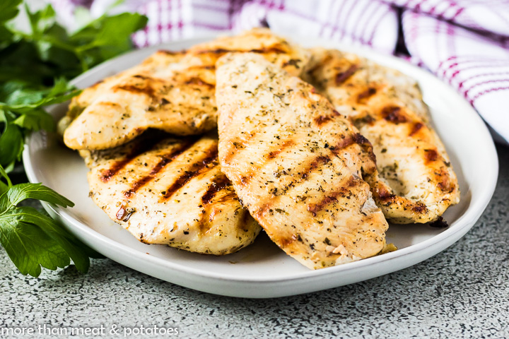 The grilled chicken flavored with an Italian marinade on a plate.