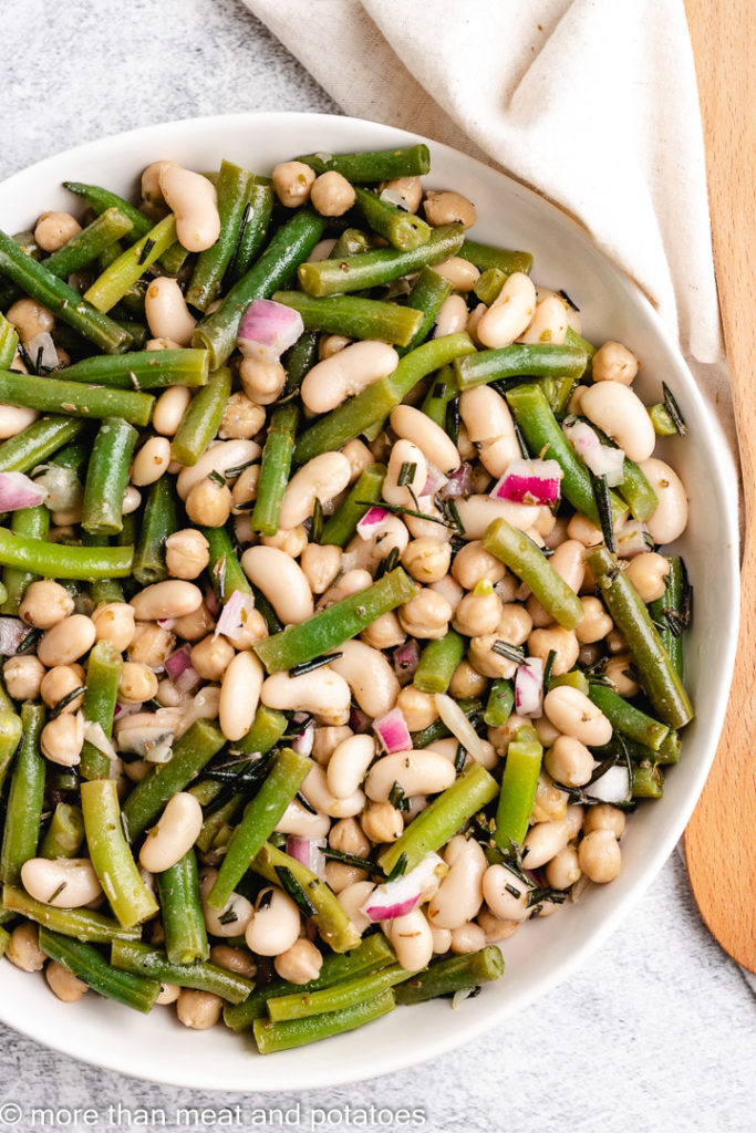 Top down view of bean salad next to a wooden spoon.