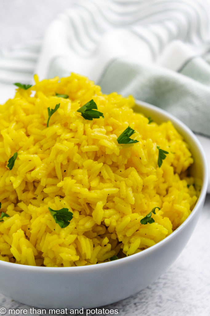 Close up of yellow rice in a blue bowl.