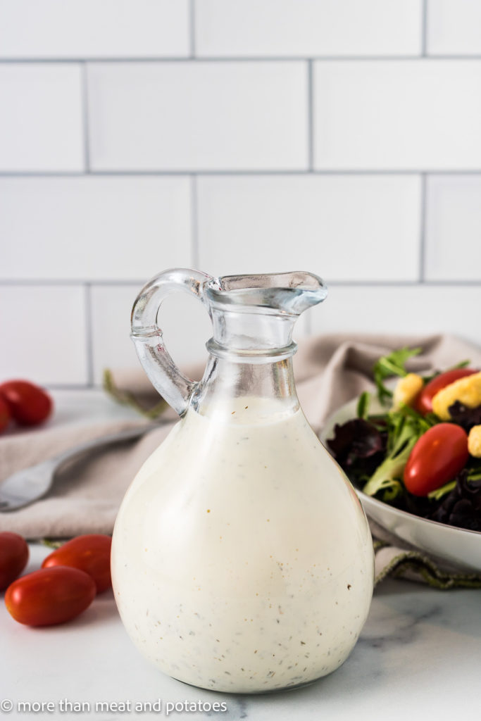 Jar of ranch dressing with a salad.