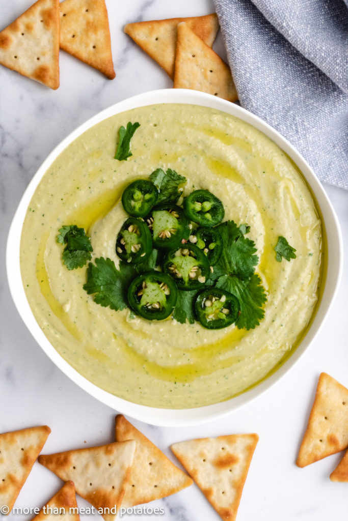 Top down view hummus topped with jalapenos and cilantro.