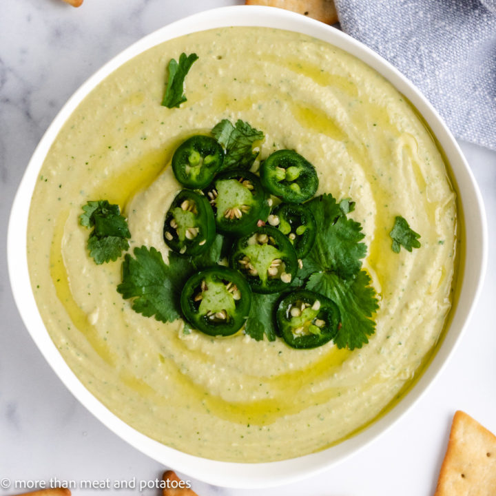 Top down view of hummus topped with cilantro and hummus.