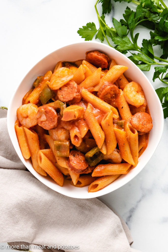 Top down view of pasta with sausage and shrimp.