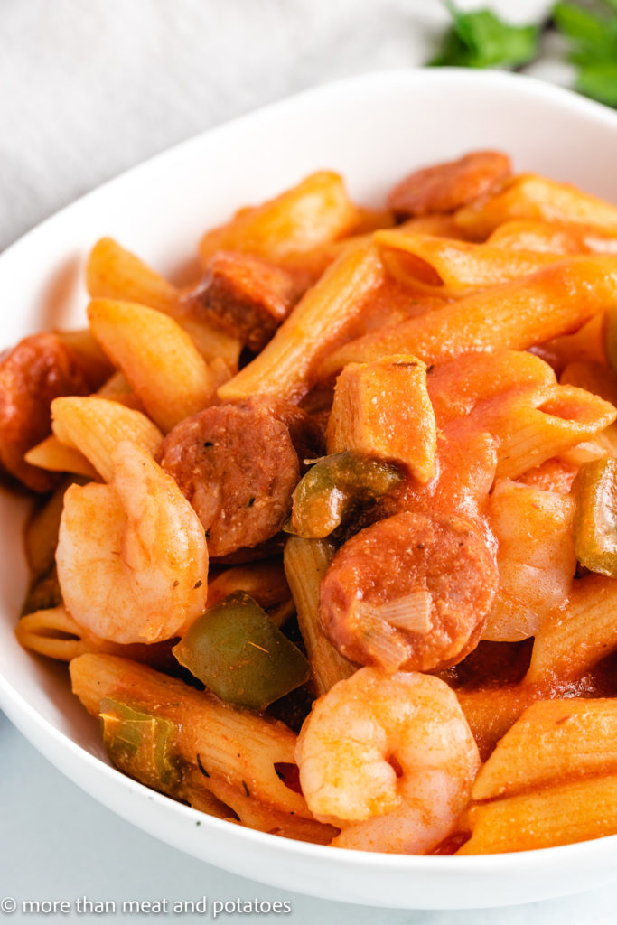 Close up view of pasta with sausage and shrimp.