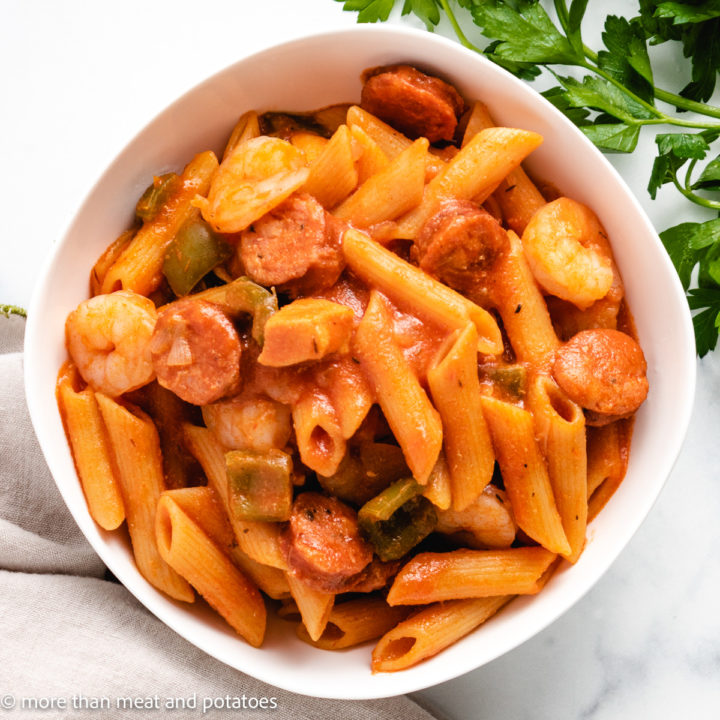 Top down view of pasta with sausage and shrimp in a serving dish.