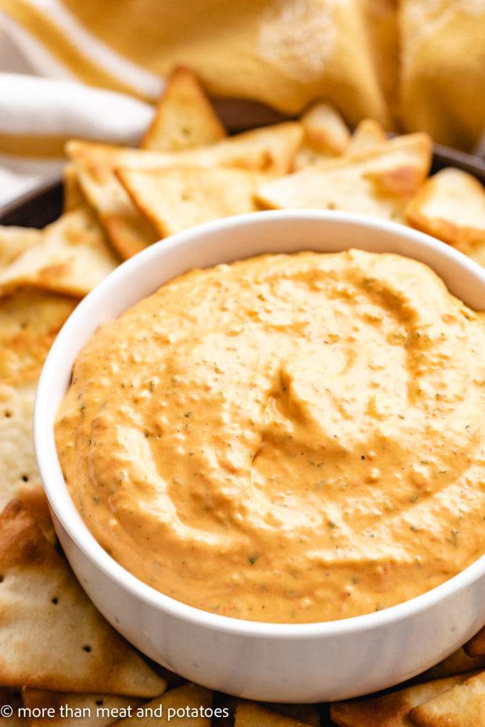 Roasted pepper dip in a bowl with pita chips.