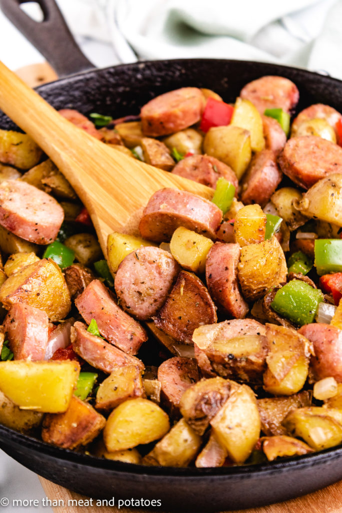 Close up view of sausage and potatoes on a wooden spoon.