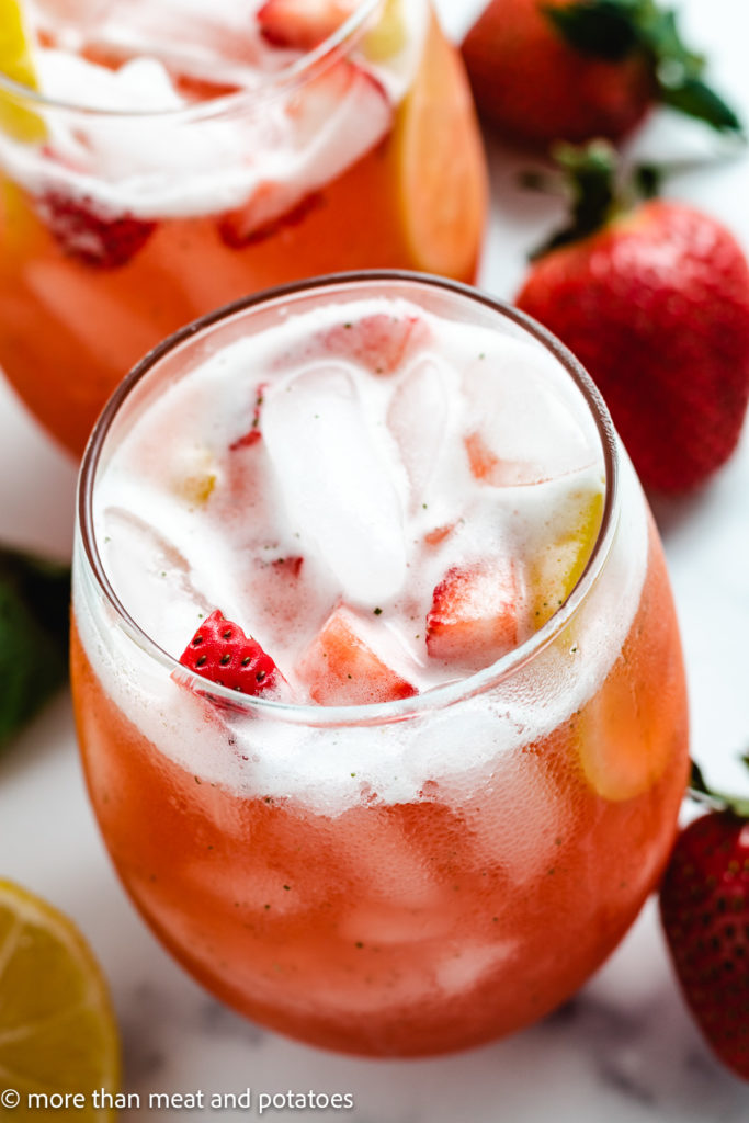 Top down view strawberry basil lemonade in a glass.