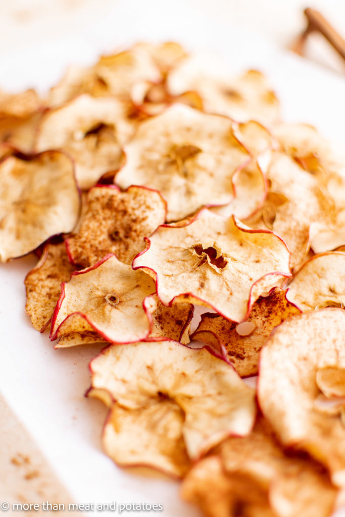 Large white plate filled with apple chips.