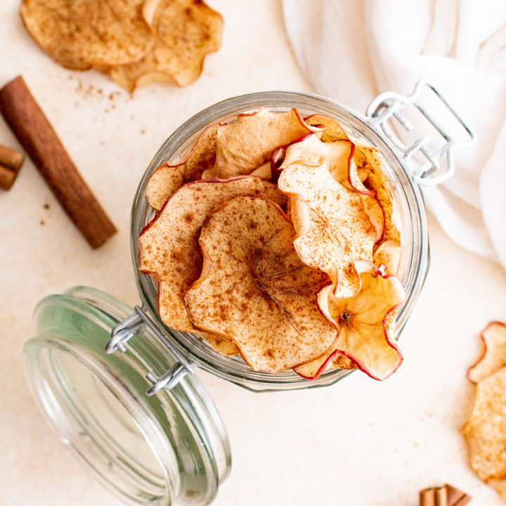 Top down view of a an open glass jar filled with dehydrated apple chips.