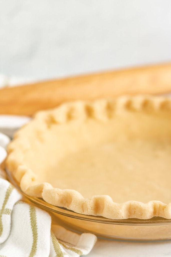 Pie crust with all butter in a glass pie dish.
