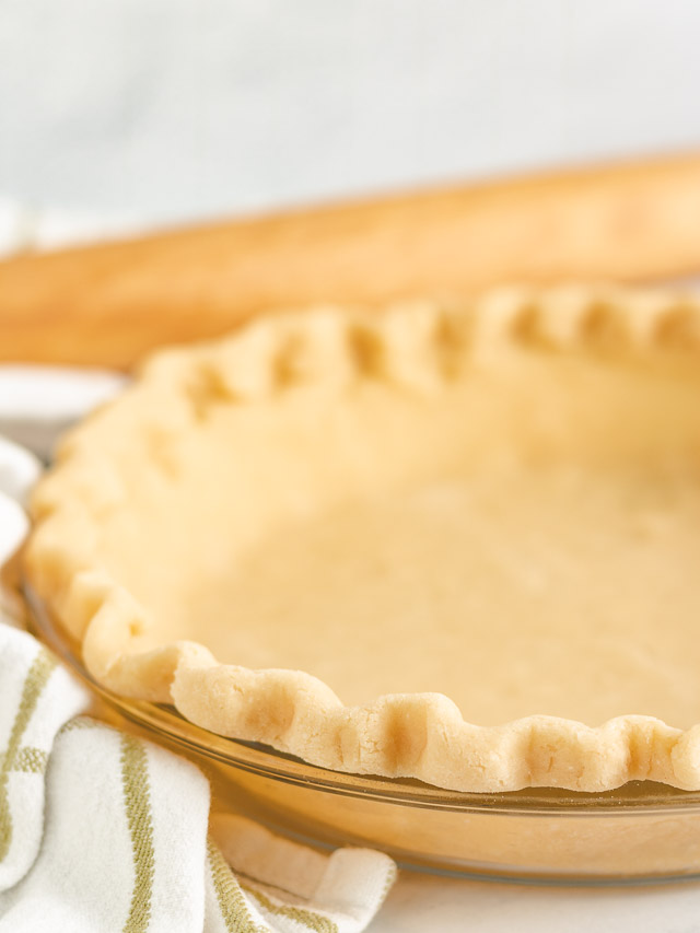 Close up of pie crust with a green and white towel in a dish.