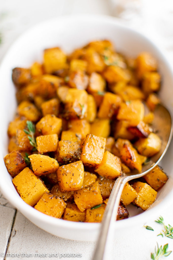 Close up of a platter of roasted butternut squash with a serving spoon.