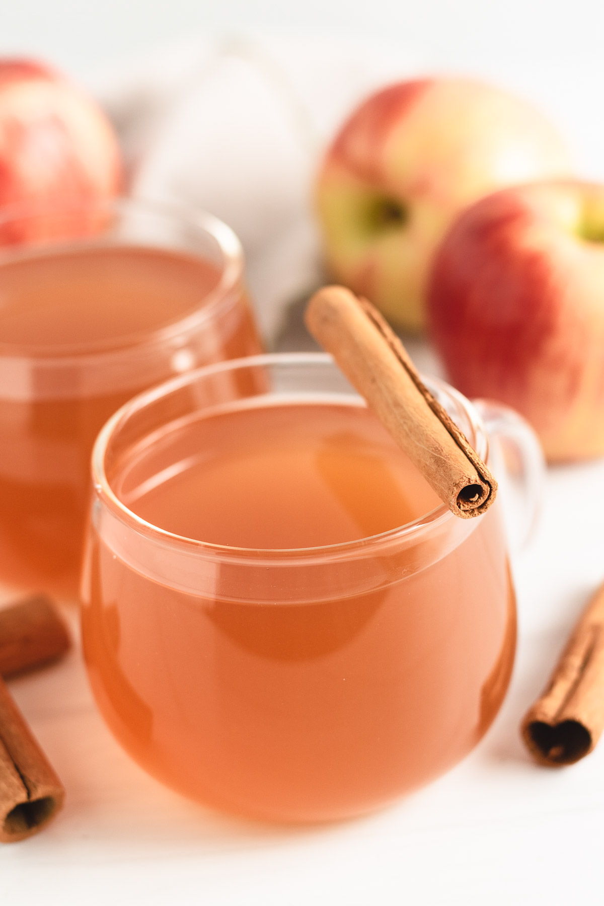 Glass mug filled with cider and a cinnamon stick.