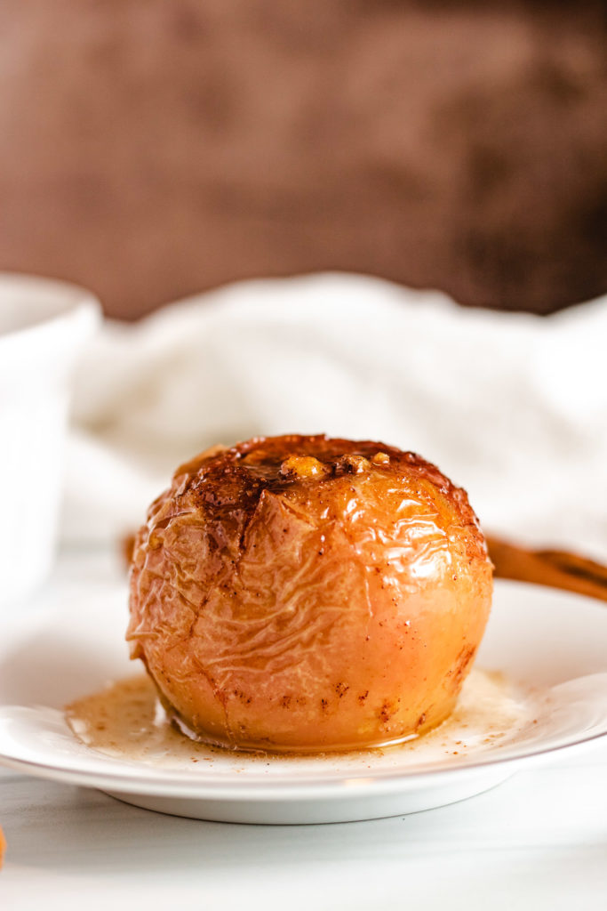 Whole baked apple on a plate.