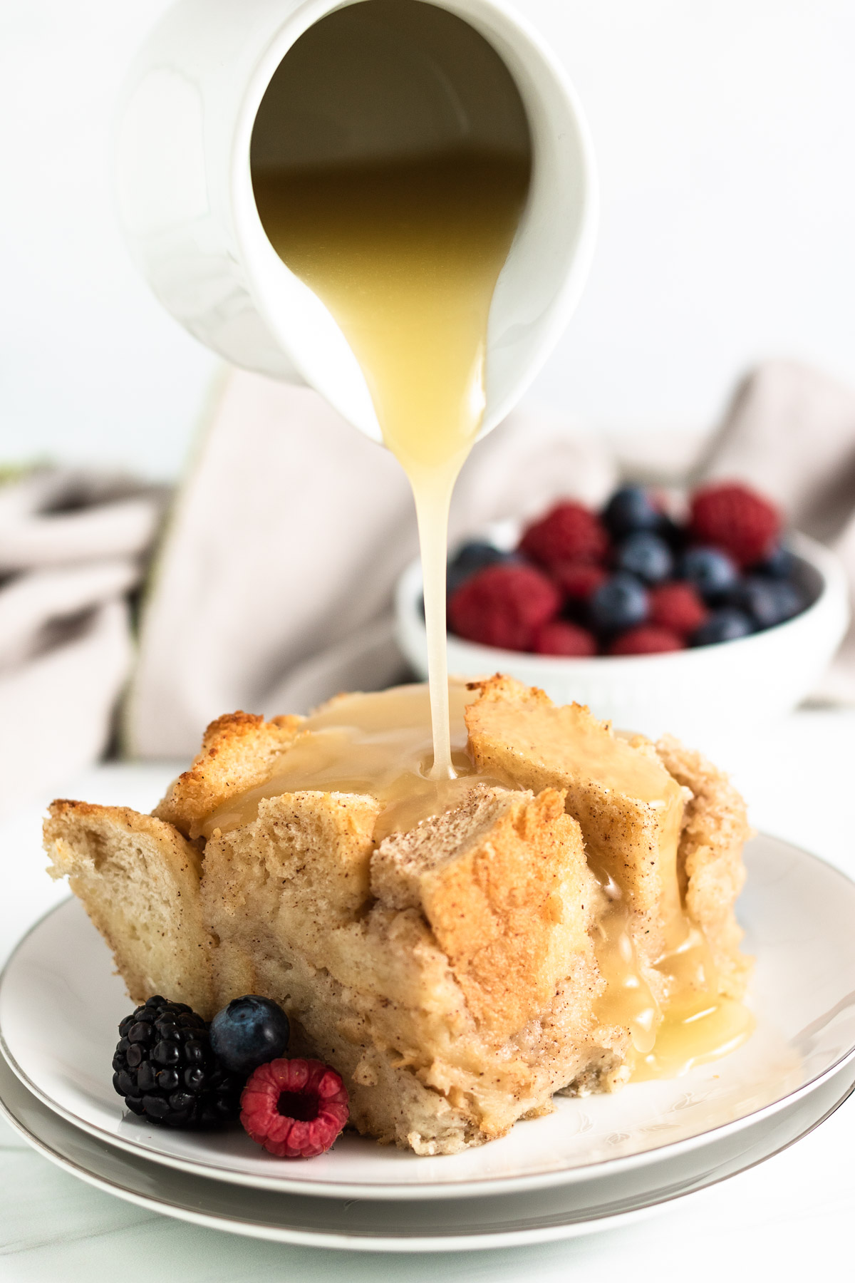 Rum sauce being poured on a plate of bread pudding.