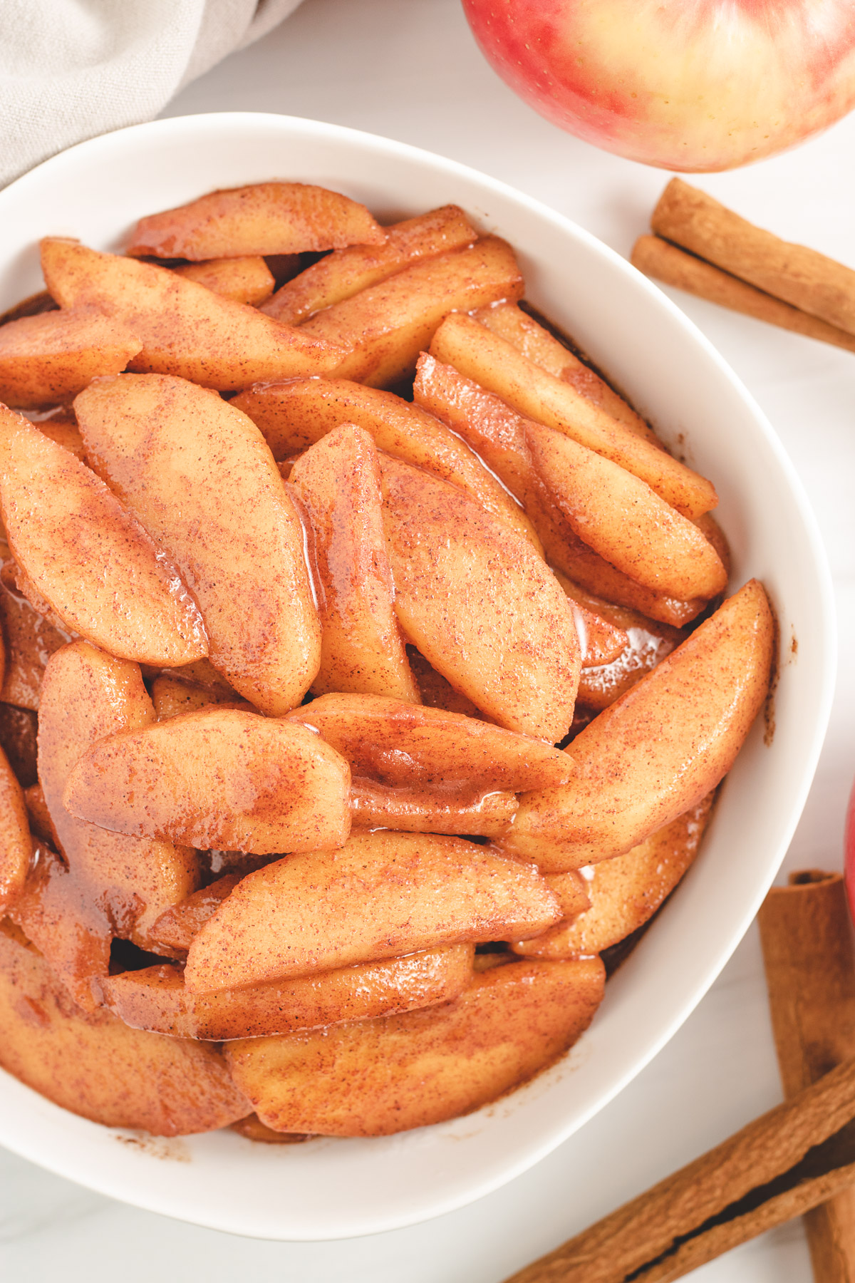 Top down view of cinnamon apples in a white bowl.