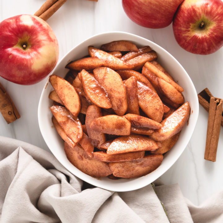 Top down view of cinnamon apples in a white serving dish.