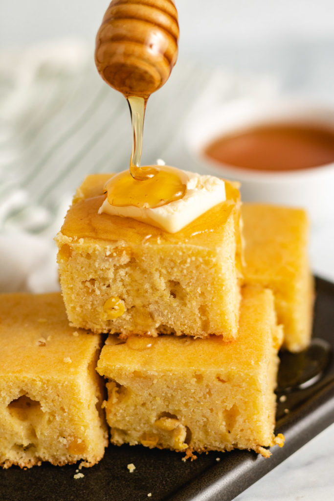 Honey being drizzle over skillet cornbread.