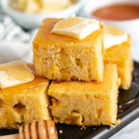 Skillet cornbread with butter on a platter.