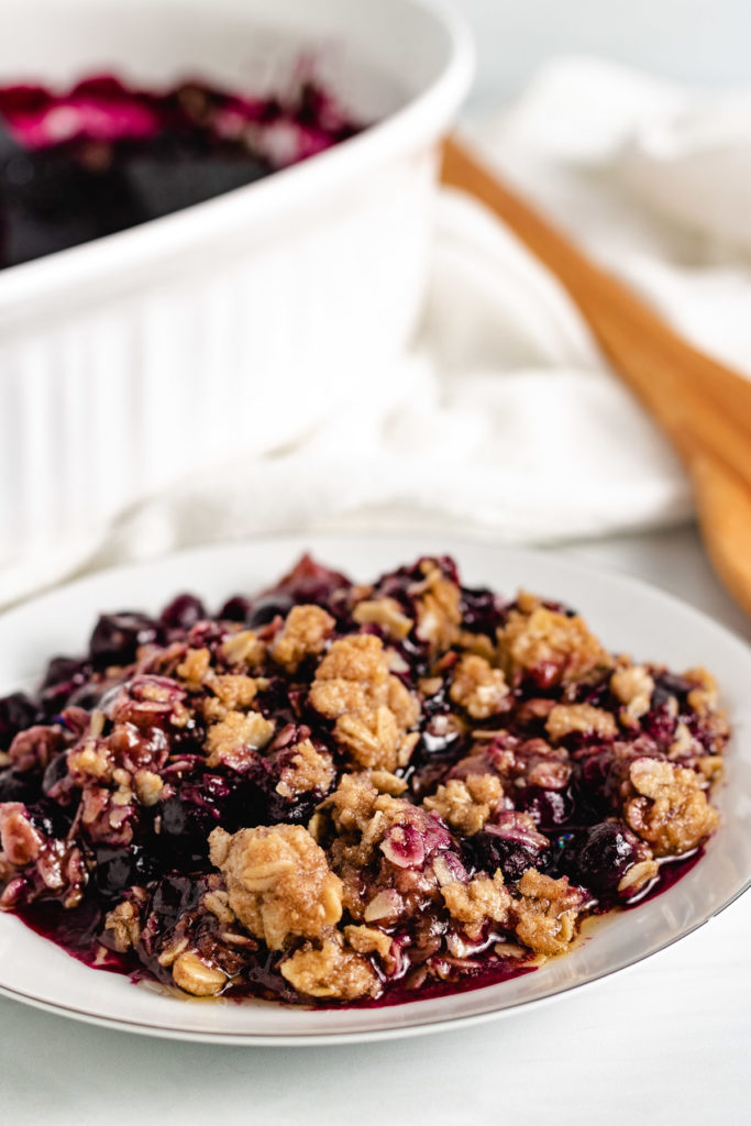 White dish filled with blueberry crisp.