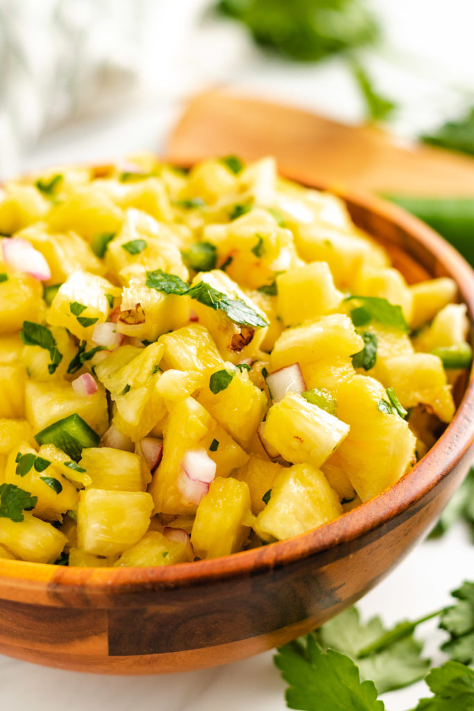 Wooden bowl filled with pineapple jalapeno salsa.