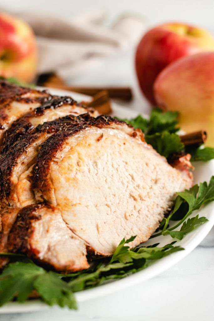 Apple cider marinated pork loin on a white plate.