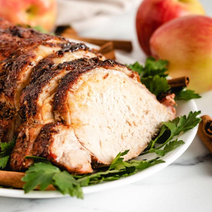 Roasted pork loin sliced on a platter.