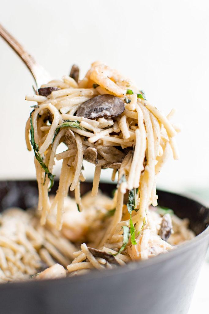 Serving spoon with mushroom shrimp pasta.