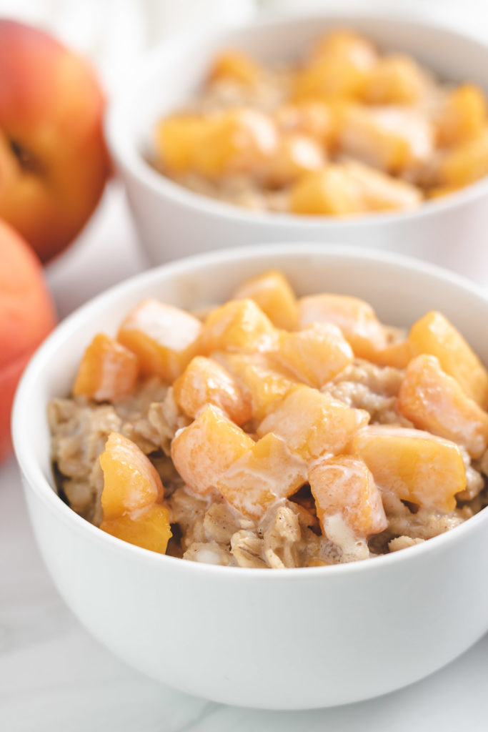 Close up view of oatmeal topped with peaches in a white bowl.