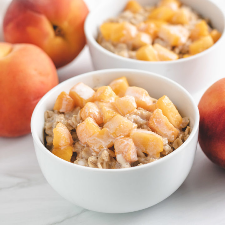 Two bowls of oatmeal topped with fresh peaches.