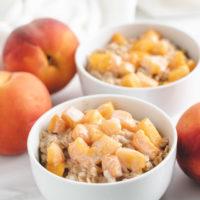 Bowls of oatmeal next to fresh peaches.