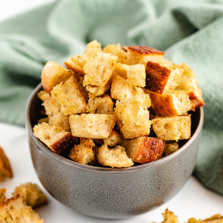 Sourdough croutons in a gray bowl with a green linen.