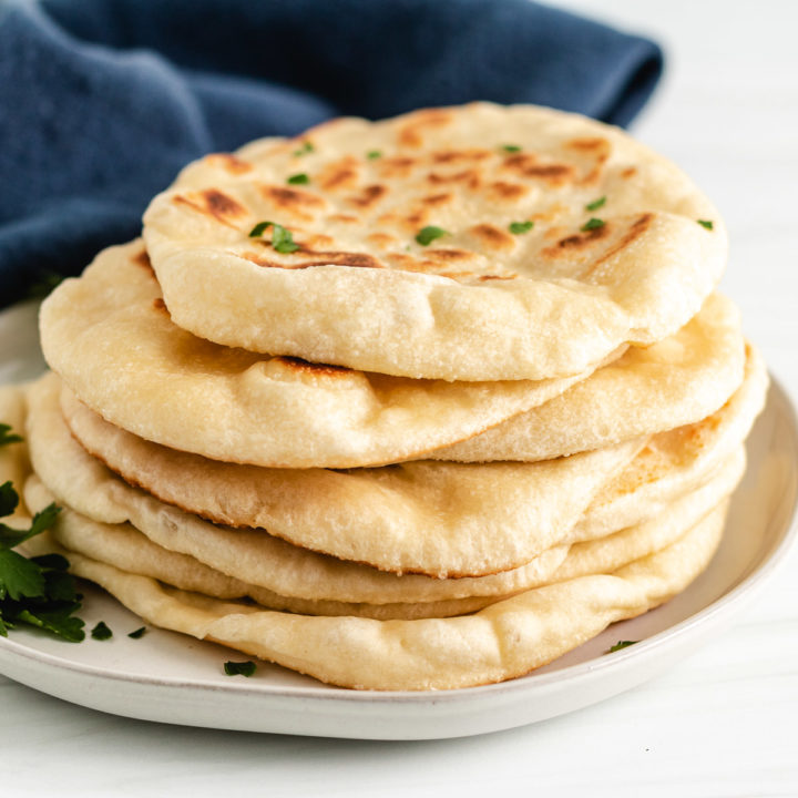 Several pieces of naan bread on a gray plate.