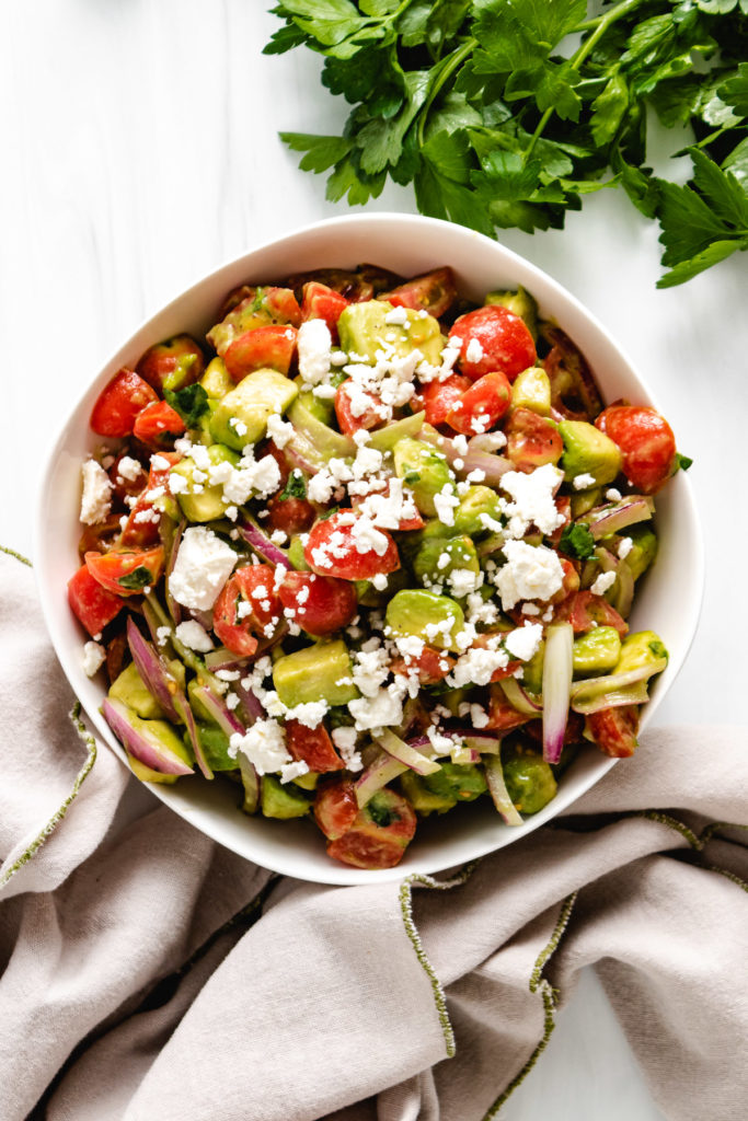 Top down view of tomato avocado salad with gray linens.