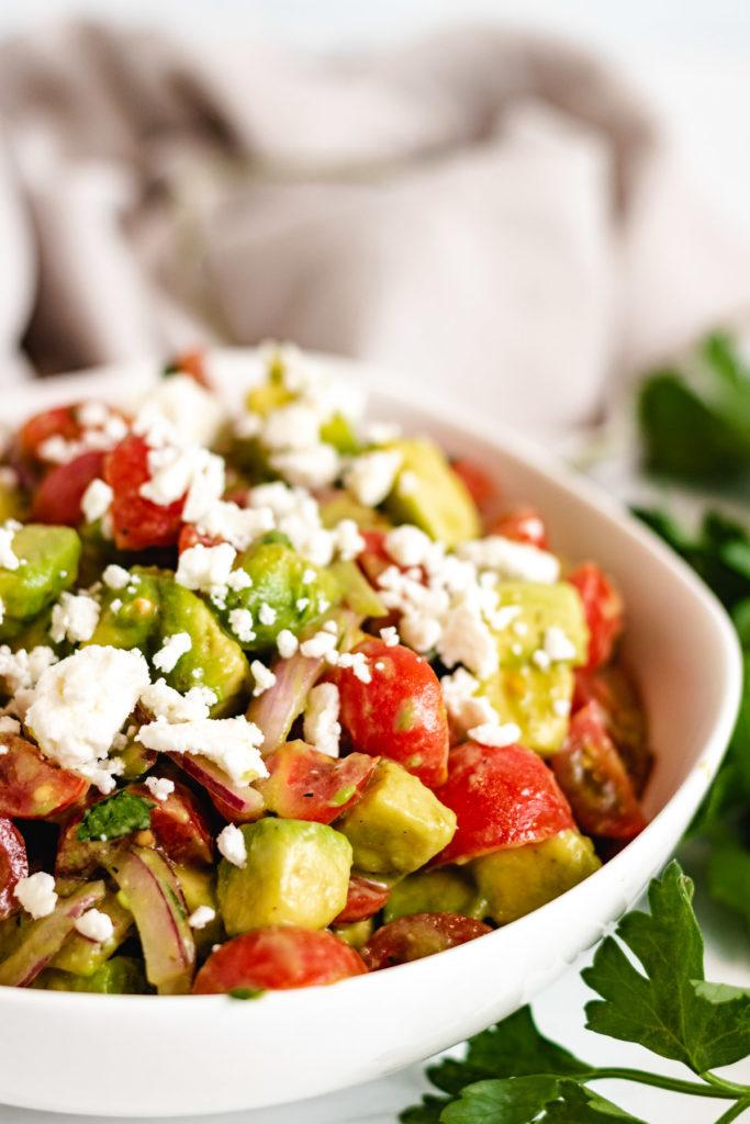 Close up of tomato avocado feta salad in a white bowl.