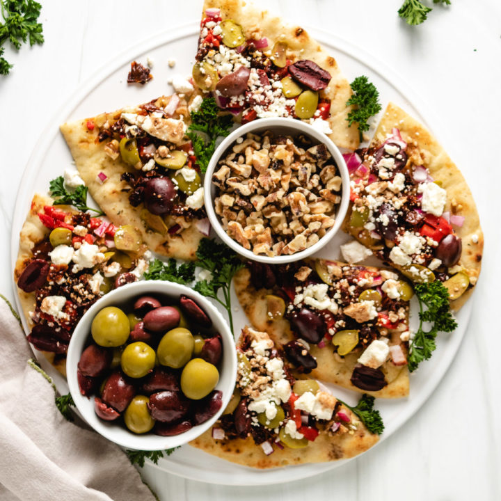 Top down view of sliced naan bread with toppings.