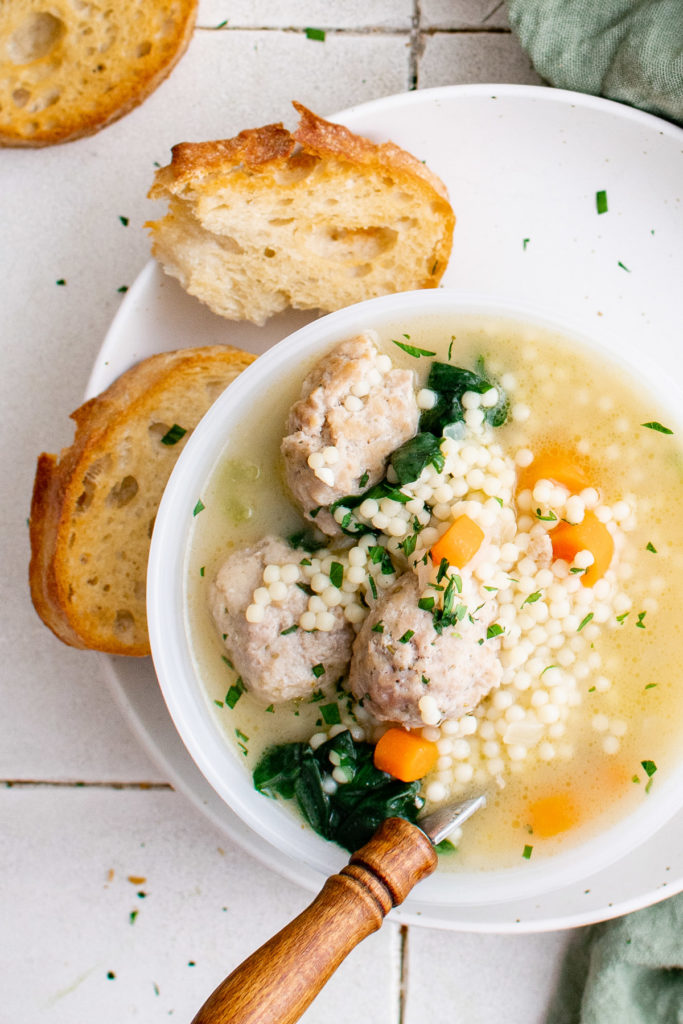 White bowl filled with soup, meatballs, and sliced bread.