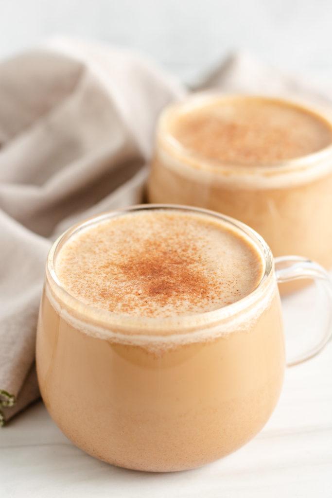 Two mugs of pumpkin spice latte.