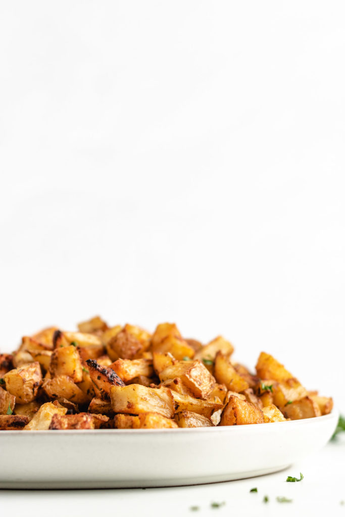 Large plate of roasted potatoes with fresh parsley.