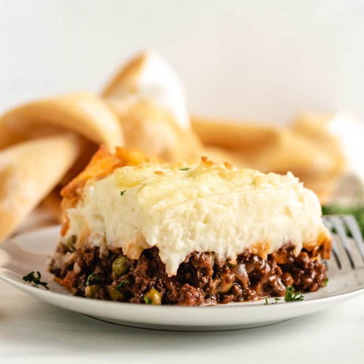 Mashed potatoes on meat filling on a white plate.