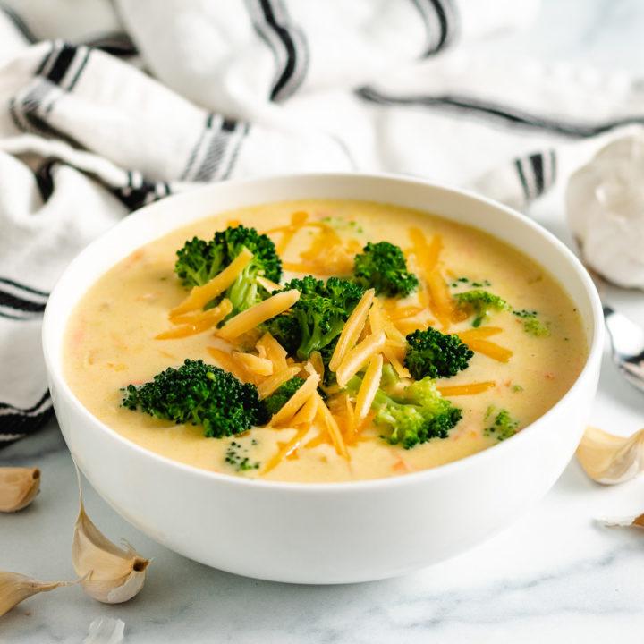 White bowl of broccoli cheddar soup.